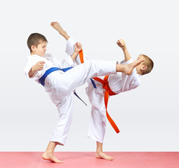 With orange and blue belt the boys are beating kicks legs