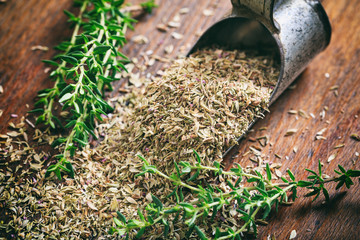 Fresh and dried thyme on a wooden table