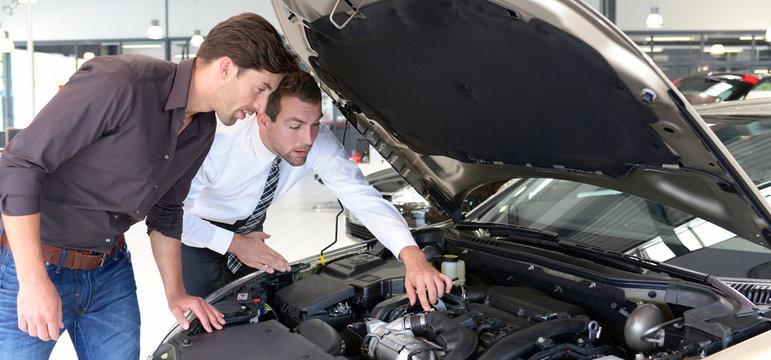 Verkaufsgespräch in einem Autohaus - Kunde mit Verkäufer unterhalten sich über Technik eines Fahrzeuges