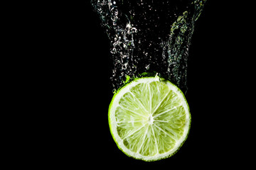 Green lime slice splashing into water.