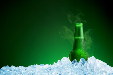 Bottle of cold beer in ice on green background