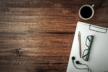 Coffee cup, glasses, pen, headphones and note on dark wood table