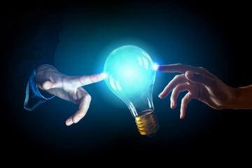 Hand pointing light bulb . Mixed media