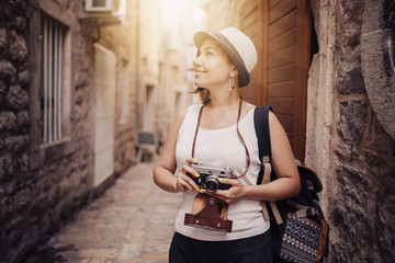 Woman traveler with vintage camera taking photo at old town