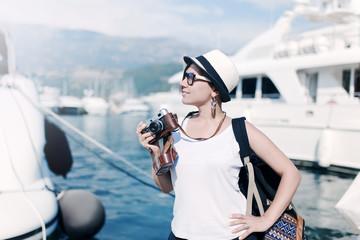 Woman with vintage camera at sea harbor