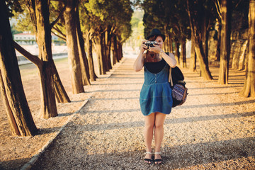 Woman with vintage camera in park alley at sunset