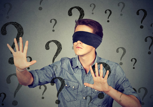blindfolded man walking through many question marks