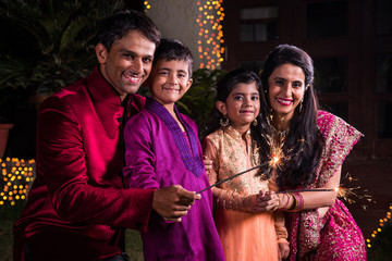 Indian Family in traditional wear playing with sparklers or phuljhadi while celebrating diwali festival, outdoor