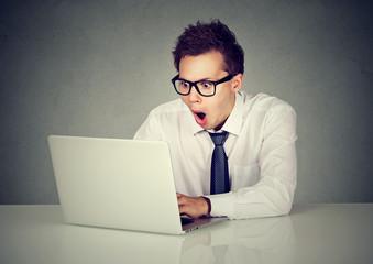 Surprised man using a laptop computer