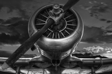 "The warplane from the past ""T-6G HARVARD"" in black and white photo, cloudy sky background"