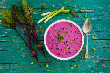 Cold soup with beetroot and vegetables on wooden table. Vegetarian food.
