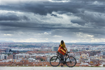 Woman with bike standing over cityscape. Fototapete