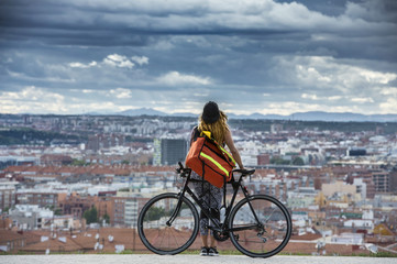 Woman with bike standing over cityscape.