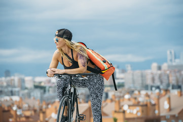 Woman with bike looking at city.
