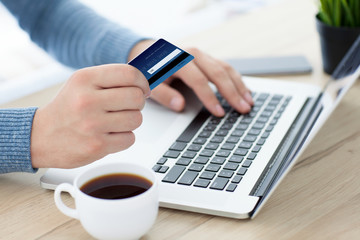 men hands with credit card on laptop keyboard and coffee