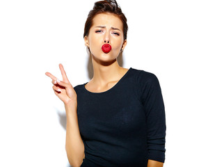cheerful smiling fashion girl going crazy in casual black clothes with red lips on white background making a duck face and showing peace sign