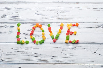 From pieces of colored candied fruits laid out the word love.