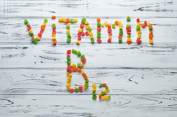 From pieces of colored candied fruits laid out the word vitamin B12.