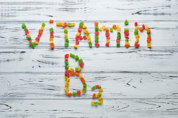 From pieces of colored candied fruits laid out the word vitamin B3.