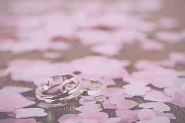 wedding rings on a wooden background with confetti Vintage Retro