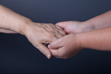 Hands of elderly and young women on black background
