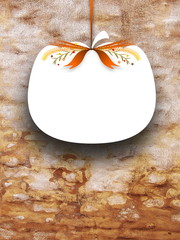 Close-up of one blank pumpkin shaped frame hanged by orange ribbon on brown weathered brick wall background