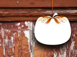 Close-up of one blank pumpkin shaped frame hanged by orange ribbon on scratched wooden background