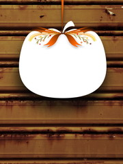 Close-up of one blank pumpkin shaped frame hanged by orange ribbon on brown rusty metal shutter background