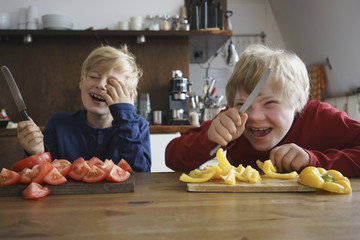 Happy brothers holding knives at table with vegetables in kitchen