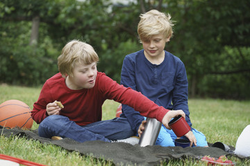 Smiling boys with insulated drink containers while sitting on blanket in park