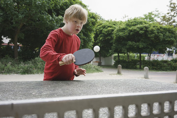 Disabled boy playing table tennis in park