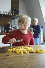 Happy disabled boy chopping yellow bell peppers with brother in background at kitchen