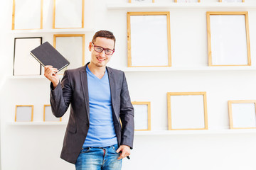 Handsome business man holding a notebook