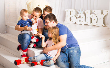 Happy family with 3 children sitting on floor of living room at home