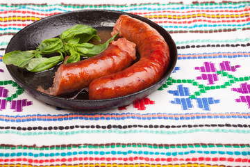 Sausages in frying pan with basil