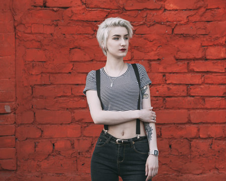 Young woman standing against red brick wall