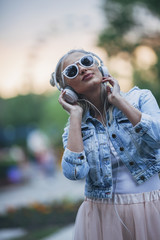 Fashionable young woman wearing sunglasses while listening to music through headphones