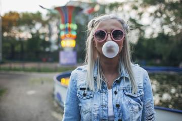 Portrait of young woman wearing sunglasses while blowing bubble gum at amusement park