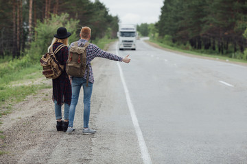 Rear view of couple hitchhiking on roadside against trees
