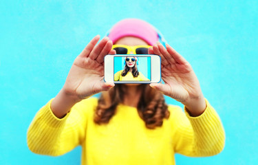 Fashion cool girl taking photo self portrait on smartphone over