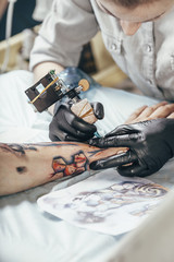 Concentrated artist tattooing design on human hand