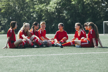 Female soccer team sitting on playing field