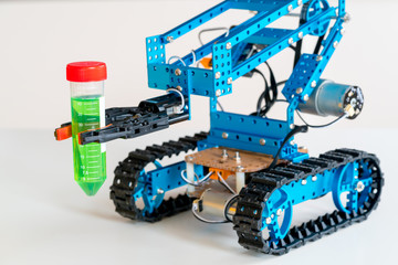 The robot arm tracks on doing an experiment with dangerous chemicals