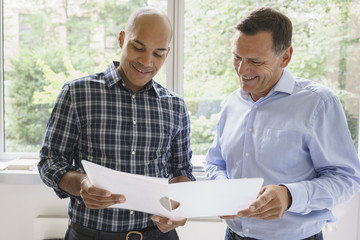Smiling businessmen discussing over file against window at creative office