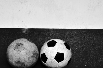 Old footballs with grunge cement wall in black and white style
