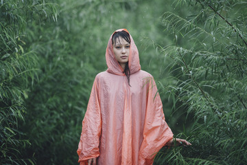Young woman wearing raincoat standing amidst plants during rainy season