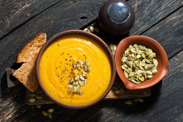 Delicious pumpkin soup on wooden table, top view