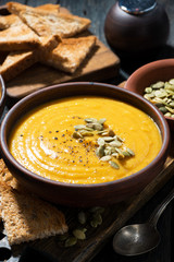 Delicious pumpkin soup on wooden table, vertical