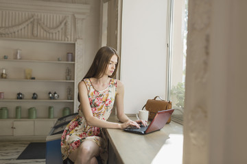 Young woman using laptop while sitting by window at cafe