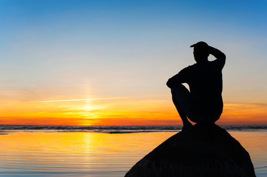 Young man silhouette sitting on the rock at sunset background